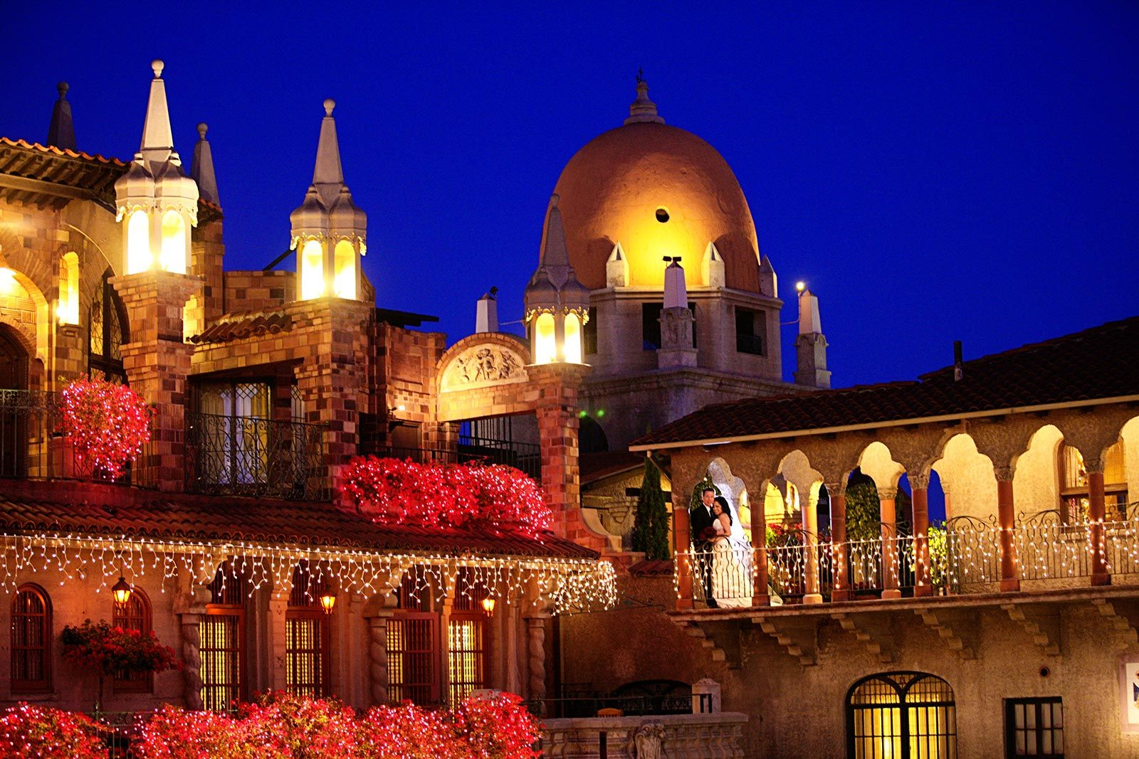 exterior of Mission Inn Hotel with bride and groom posing for pi