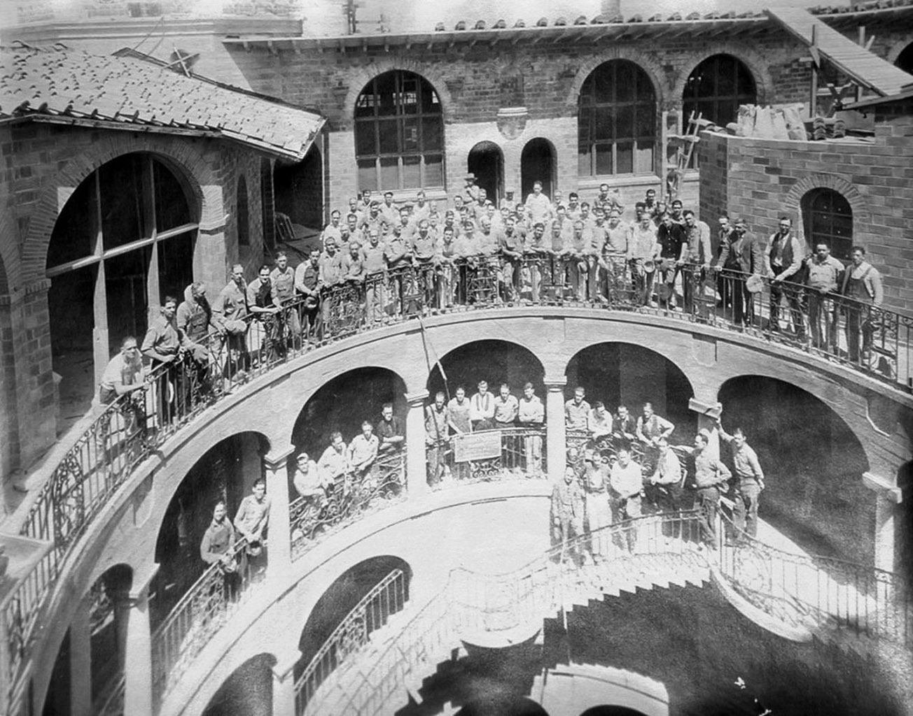 large group of men standing on exterior balcony and stairs of Mi