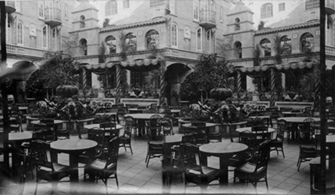 vintage image of exterior patio of Mission Inn with tables and c