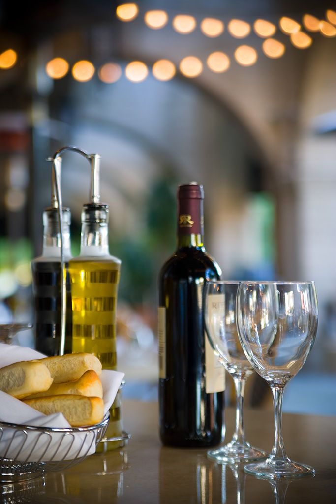 table with wine glasses and bread sticks