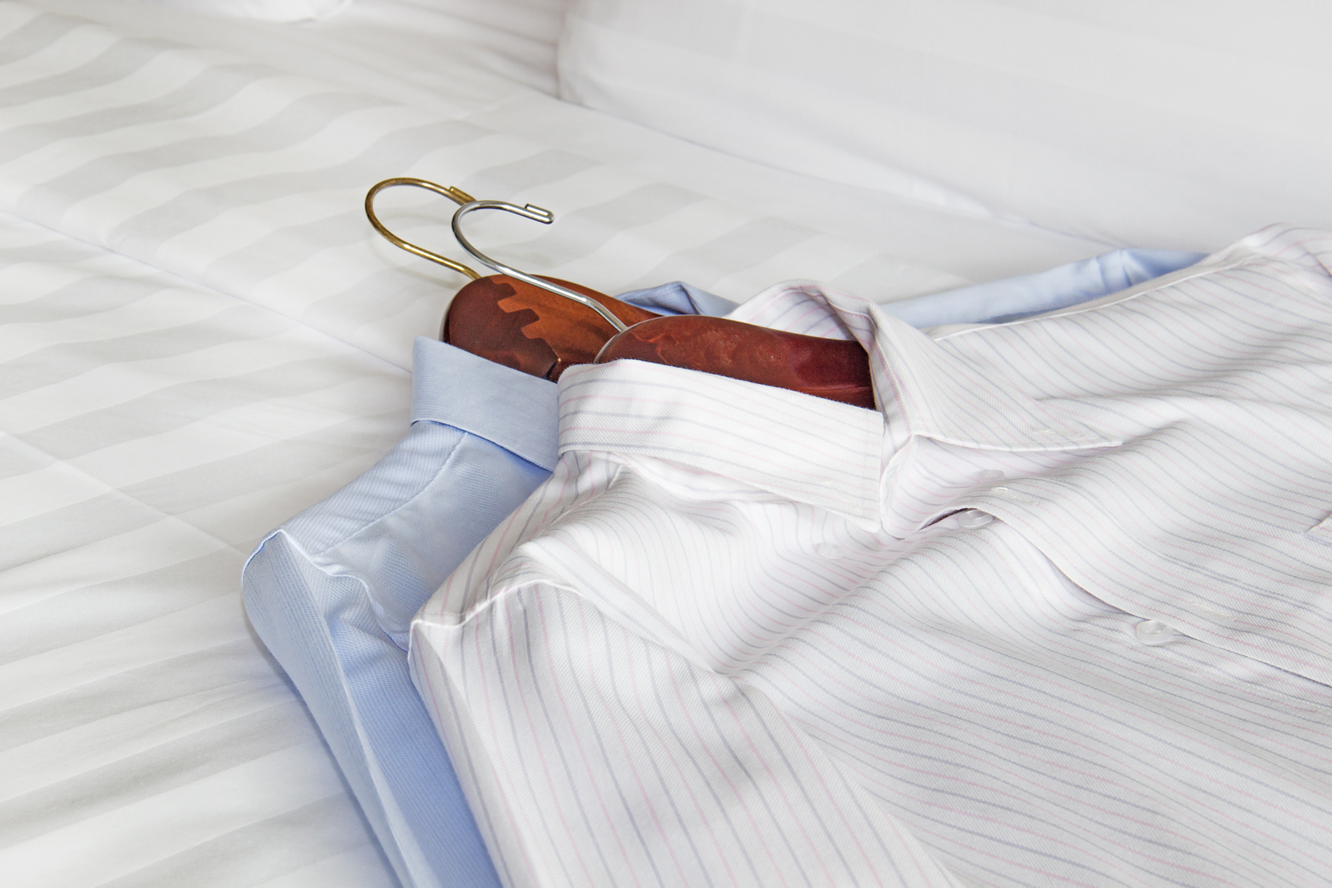 two dress shirts on hangers laying on bed