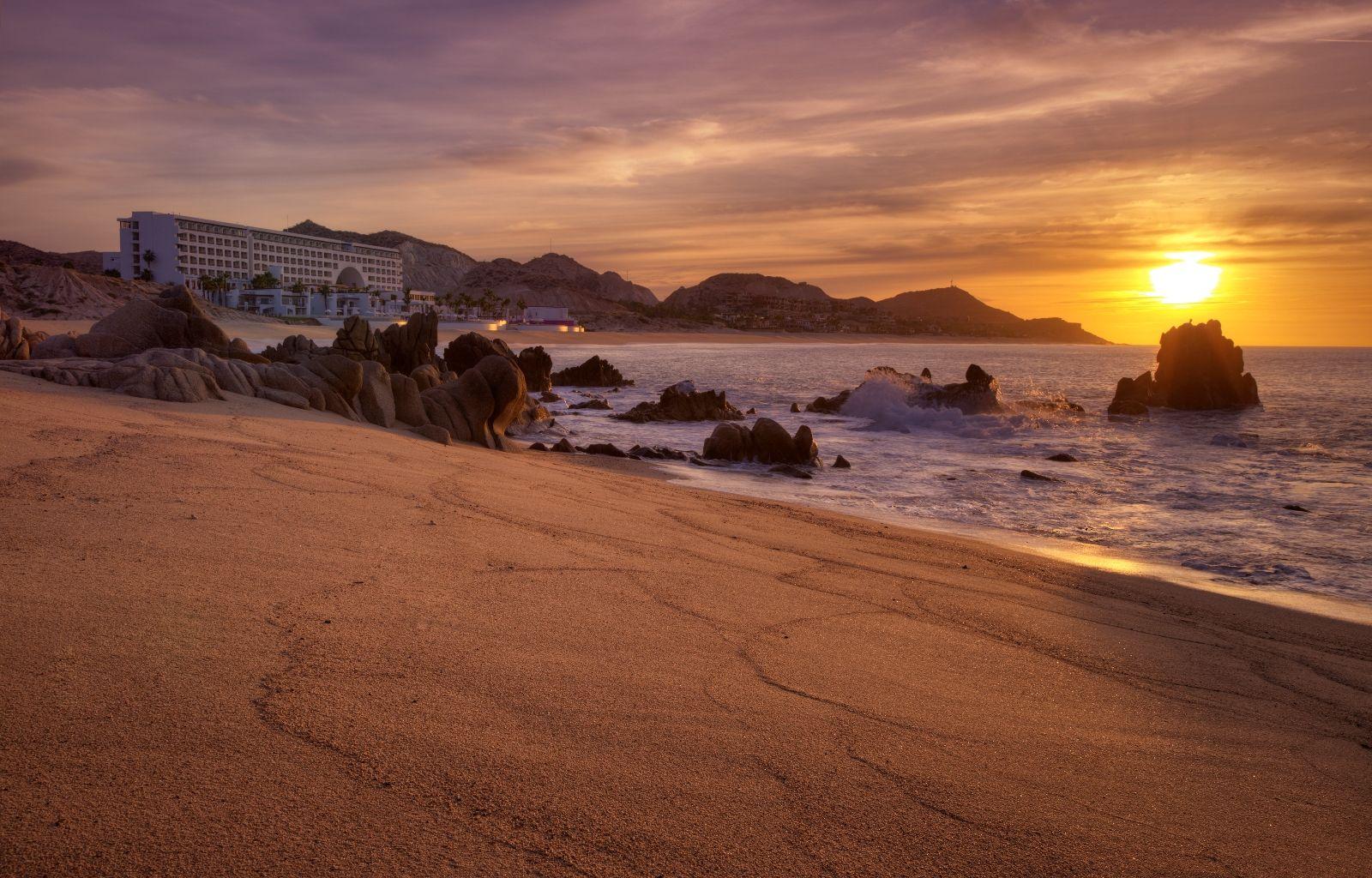 rocks in an ocean by a sandy beach