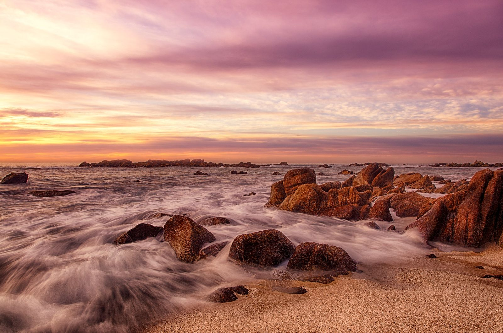 water rushes by rocks near a beach front
