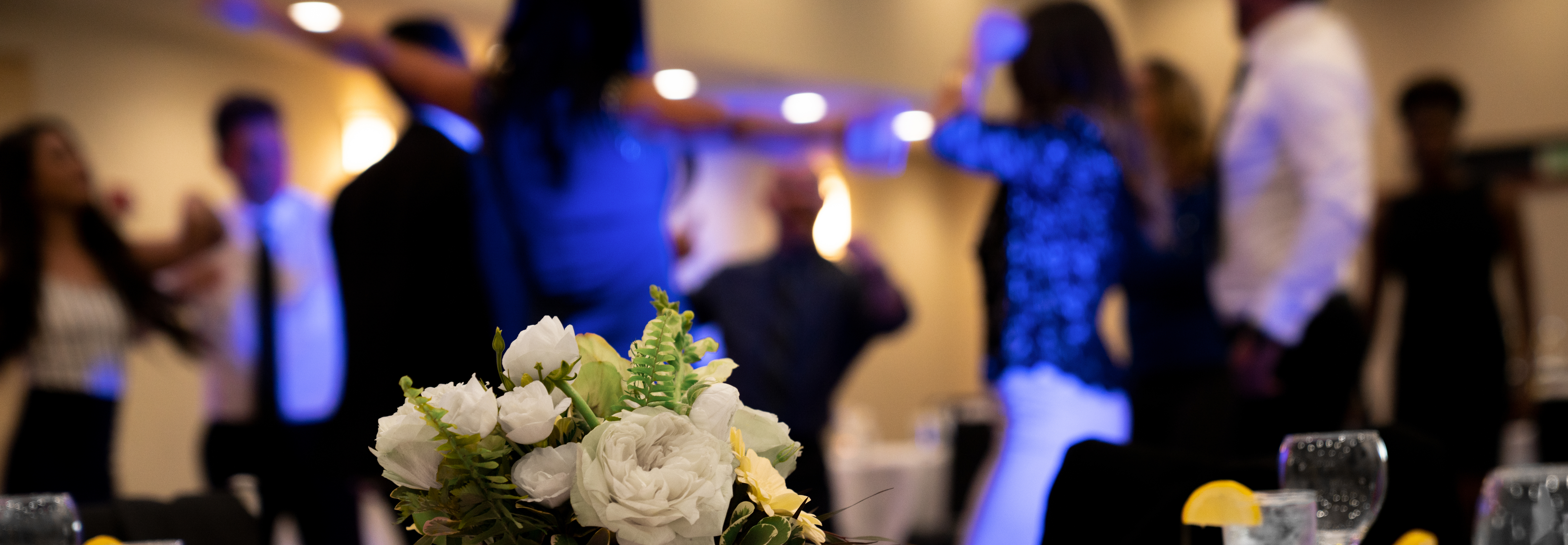 people dancing by flowers on a table