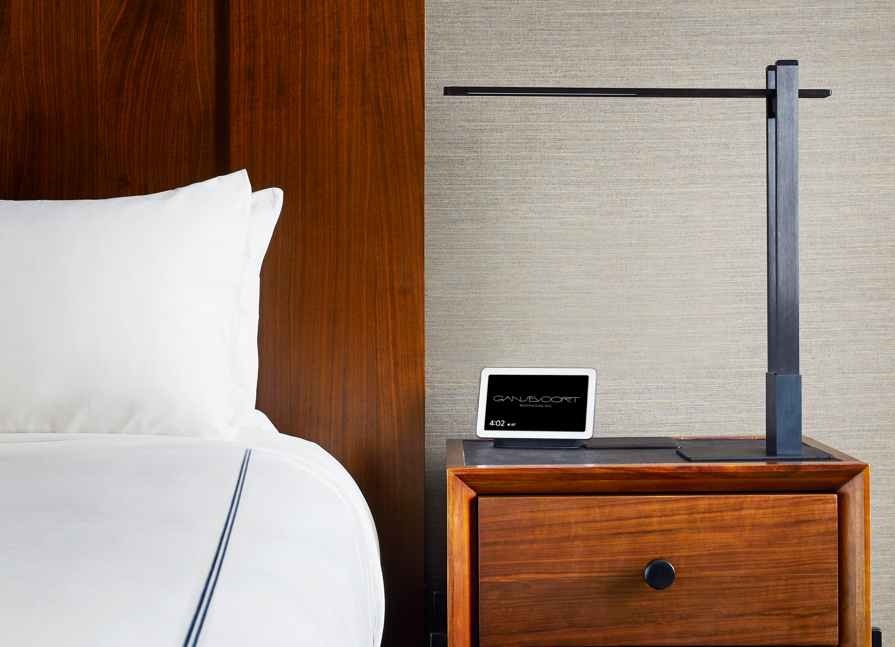 a smart device next to a hotel bed