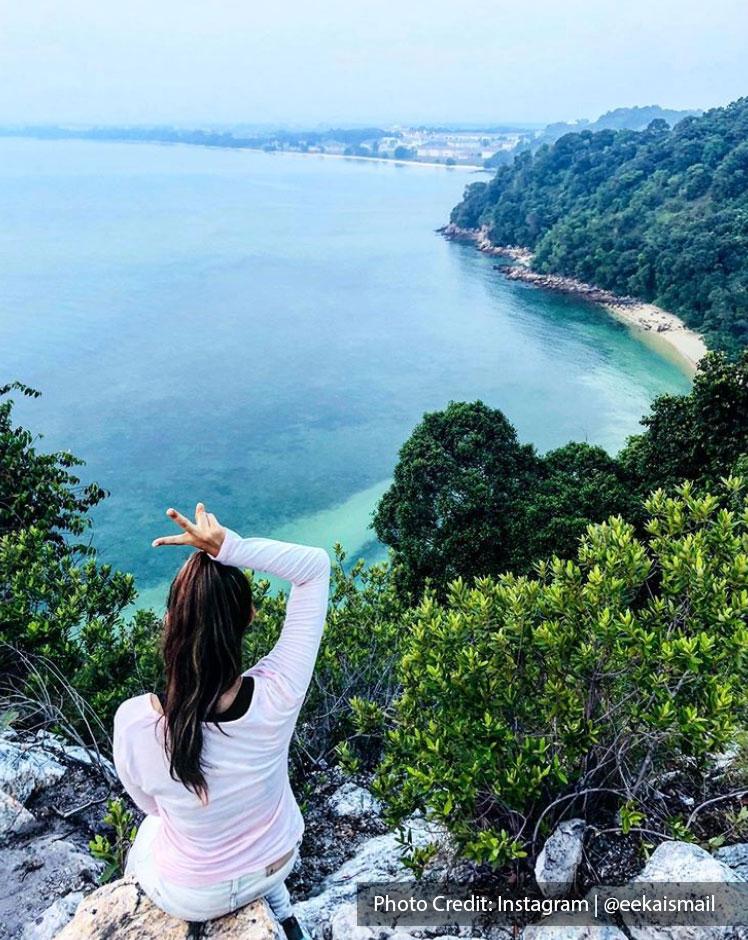 girl sitting on hill of cape rachado lighthouse port dickson