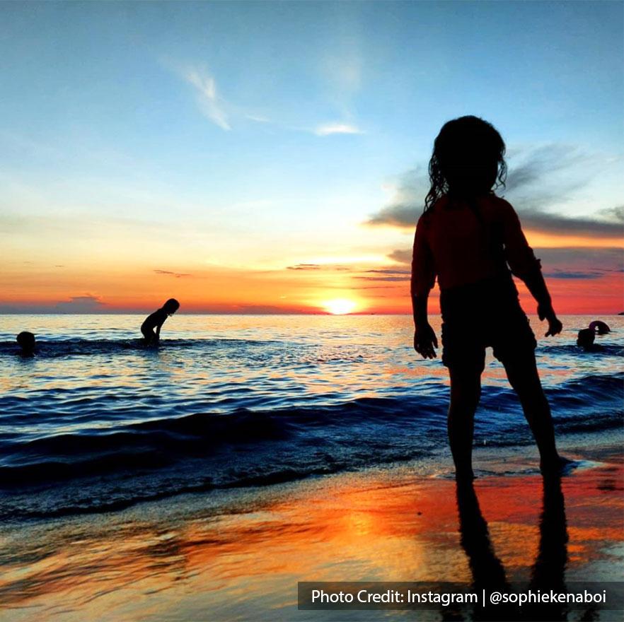 Kids playing at Teluk Kemang Beach during sunset