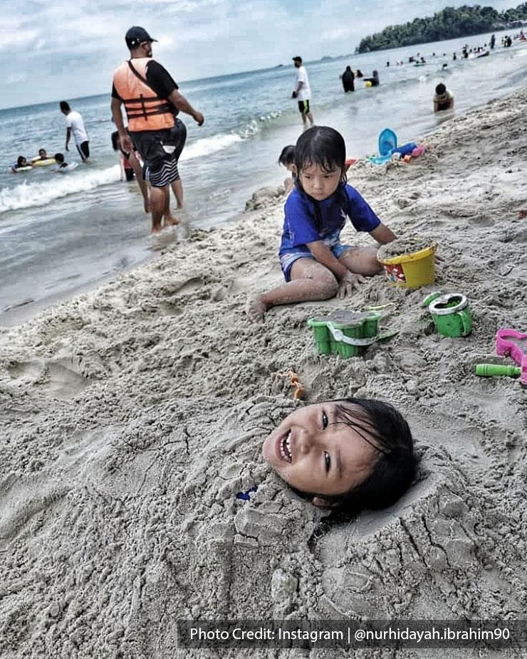 Kids playing with sand at Teluk Kemang Beach