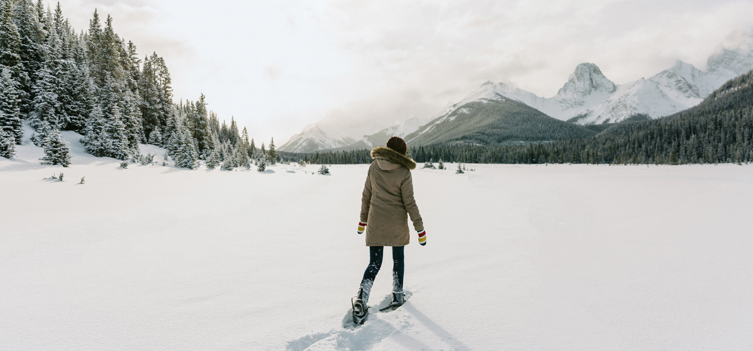 woman snowshoeing among beautiful Canmore mountains