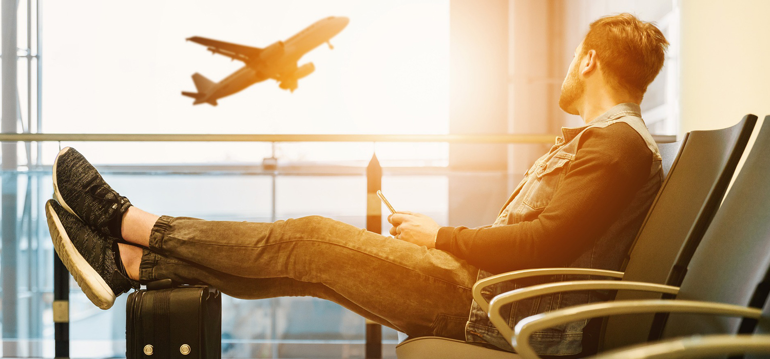 man sitting at an airport watching planes