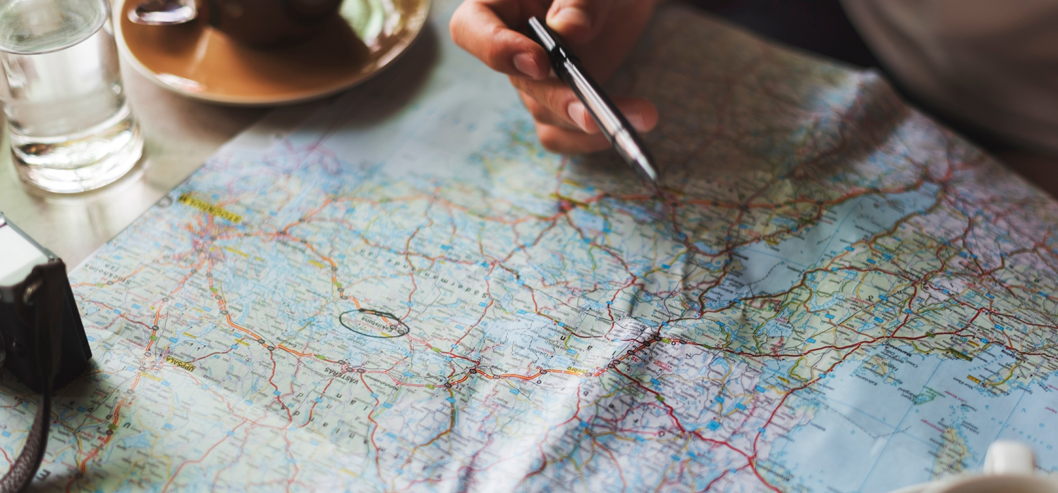 someone with a pen over a map planning a vacation