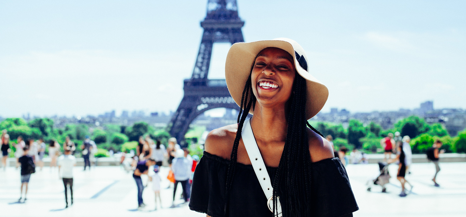 woman smiling in front of Eiffel tower in paris
