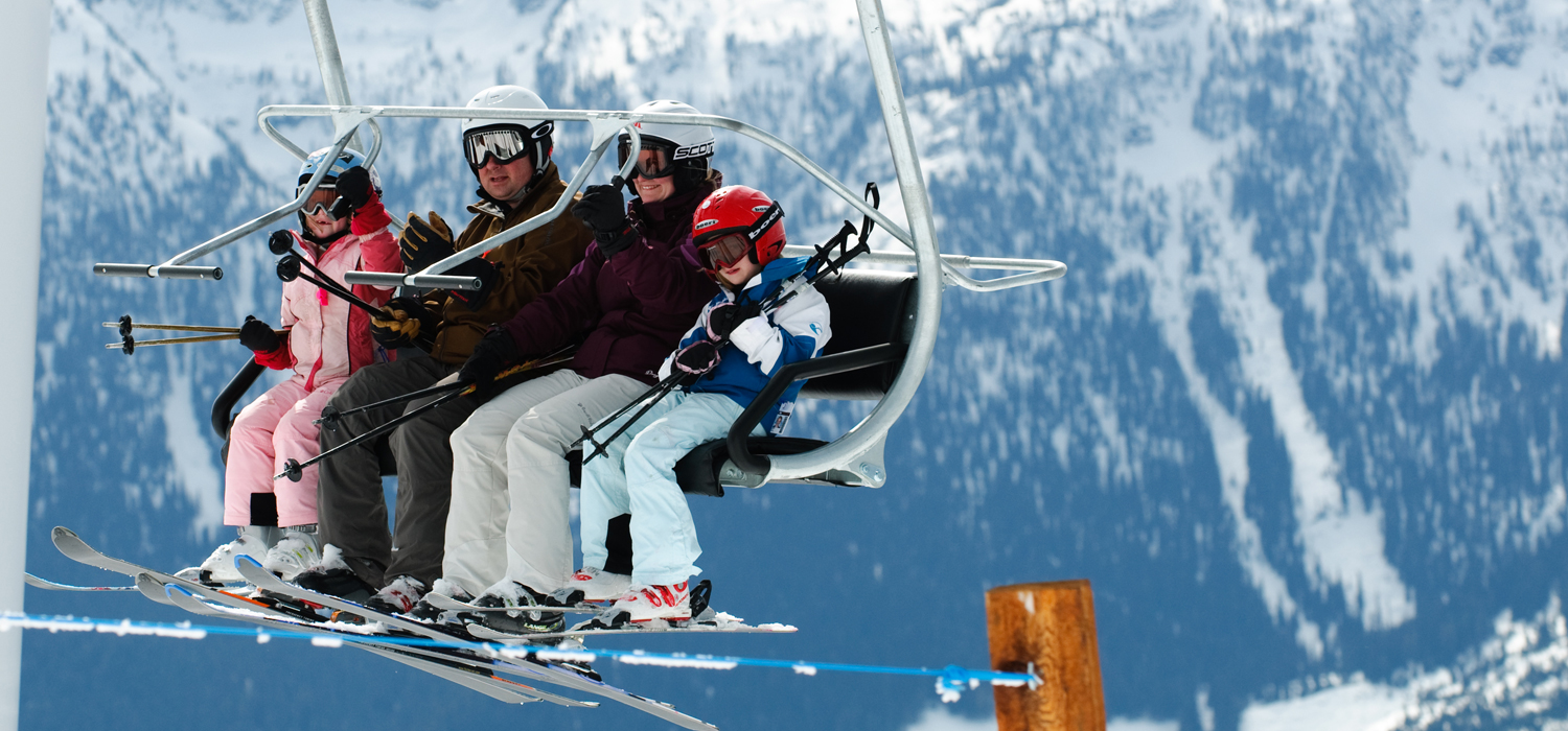 family skiing revelstoke together on chair lift