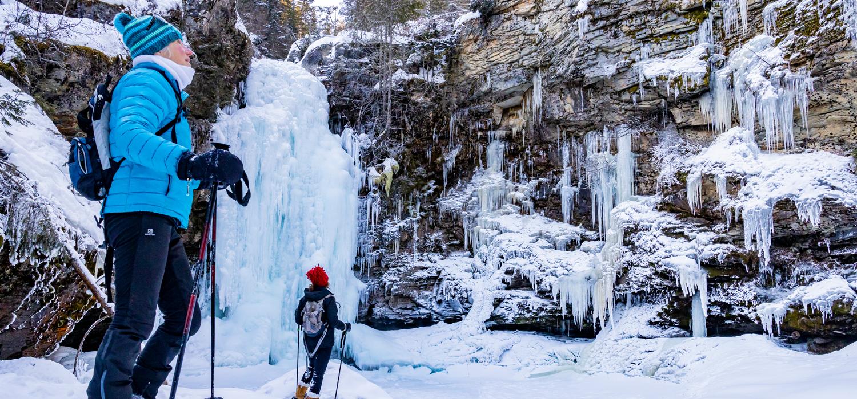 people snowshoeing to a frozen waterfall in Revelstoke
