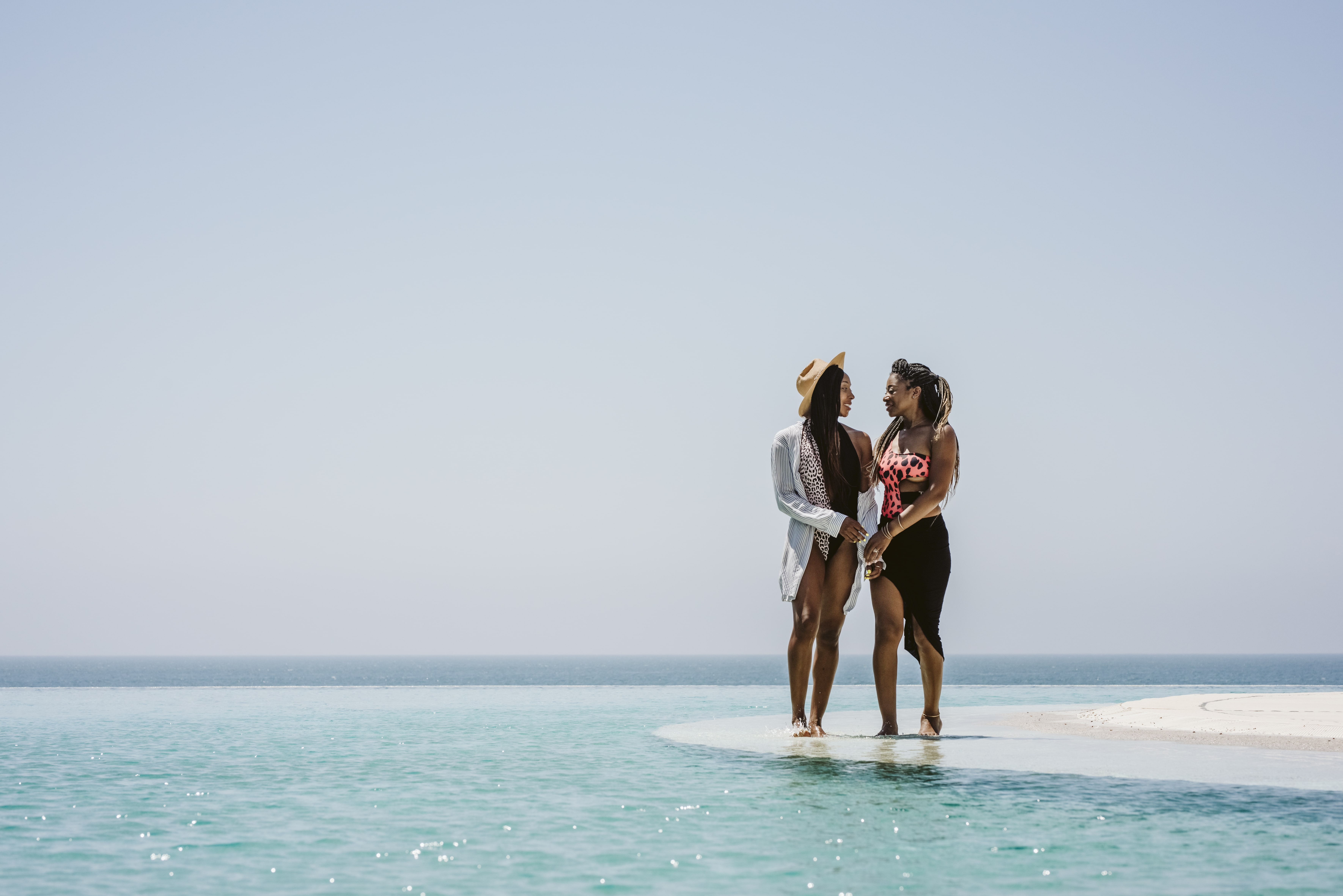 two woman stand with their feet in the ocean