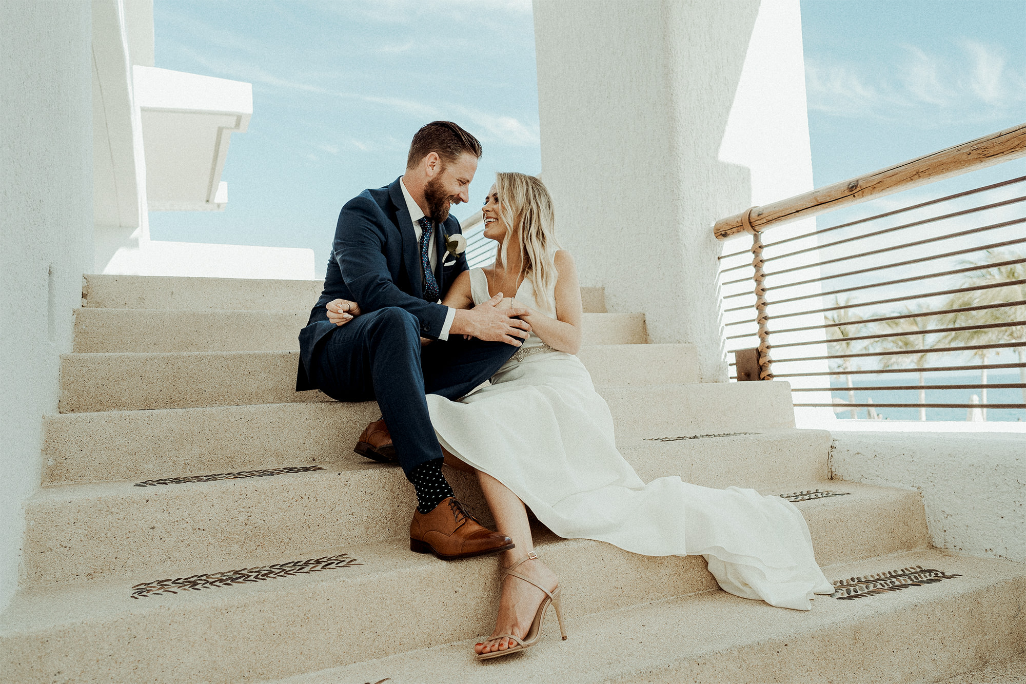 a groom and bride sitting on a stair case