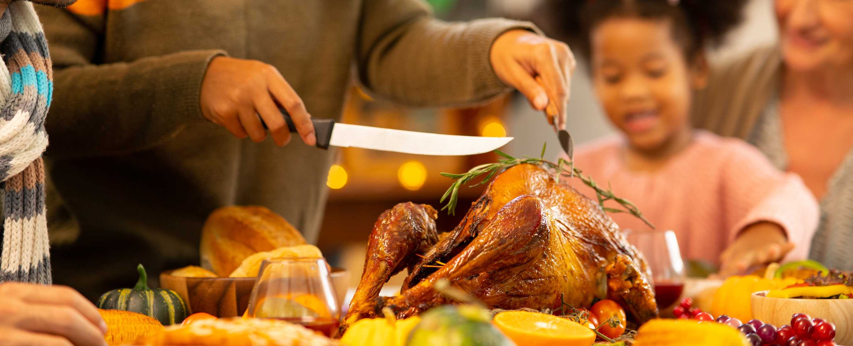 person cutting into thanksgiving turkey