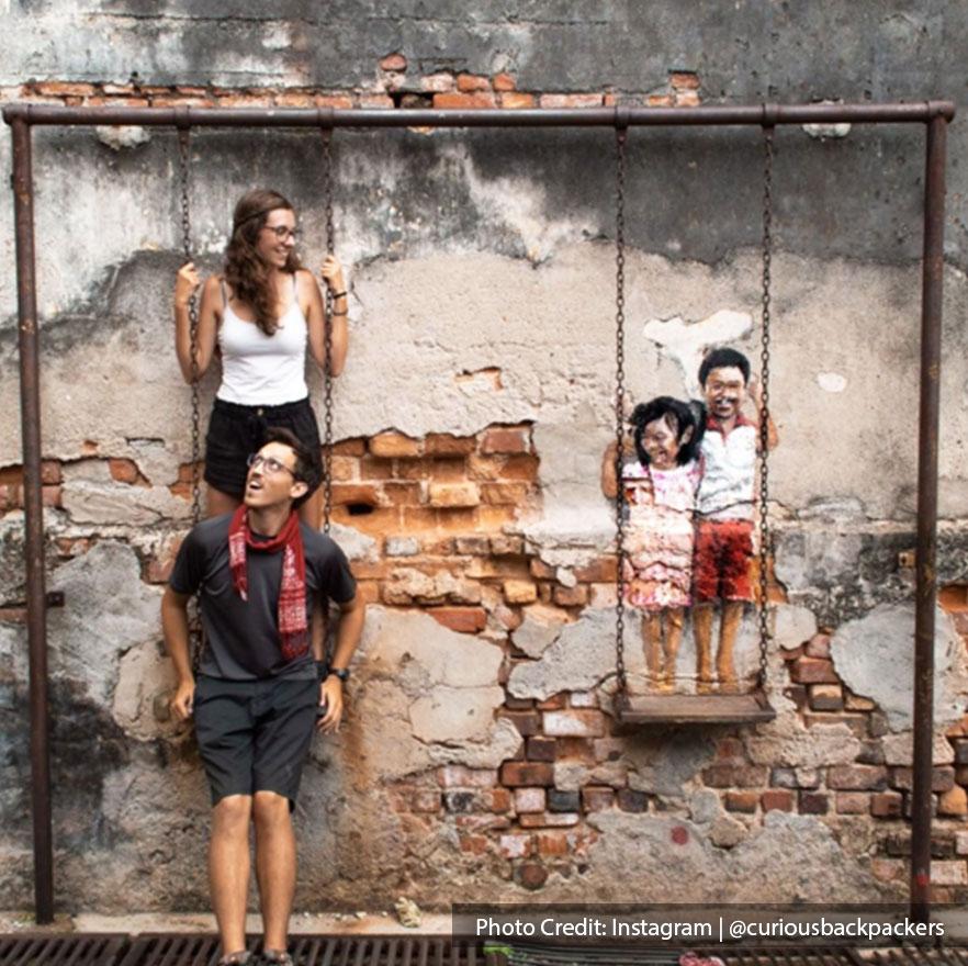 Siblings on a swing mural art in Penang by local artist Louis Gan.
