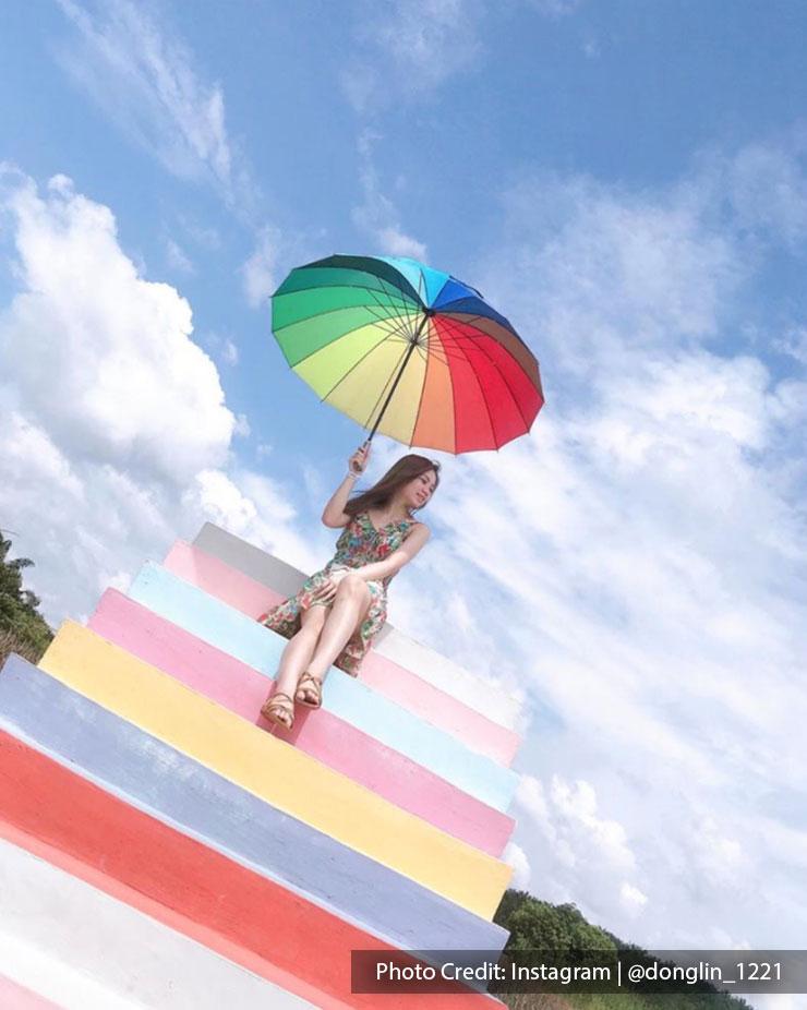 woman with rainbow coloured umbrella sky ladder pineapple farm port dickson