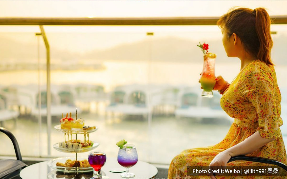 A woman enjoying beautiful sunset and beverage at Lexis Hibiscus Resort's balcony