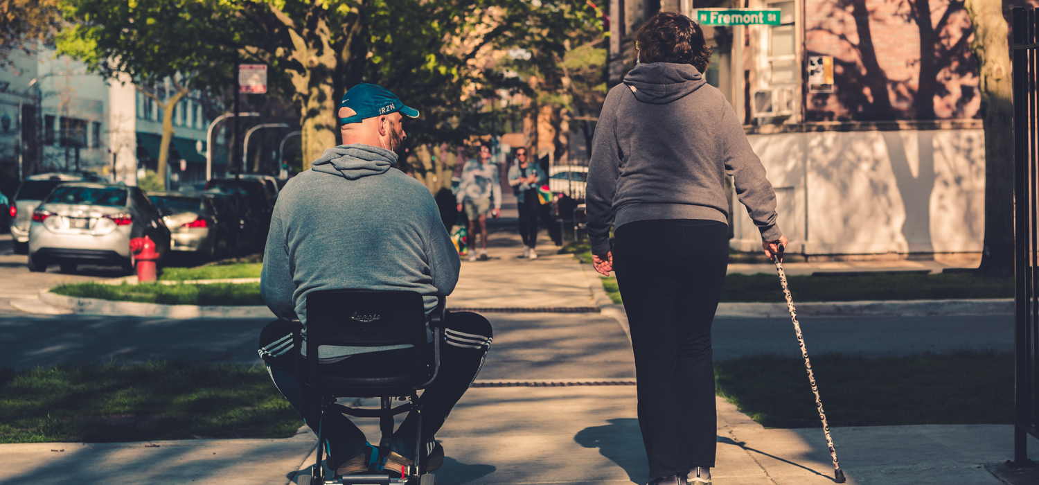 man in a mobile chair and women with a cane going for a stroll