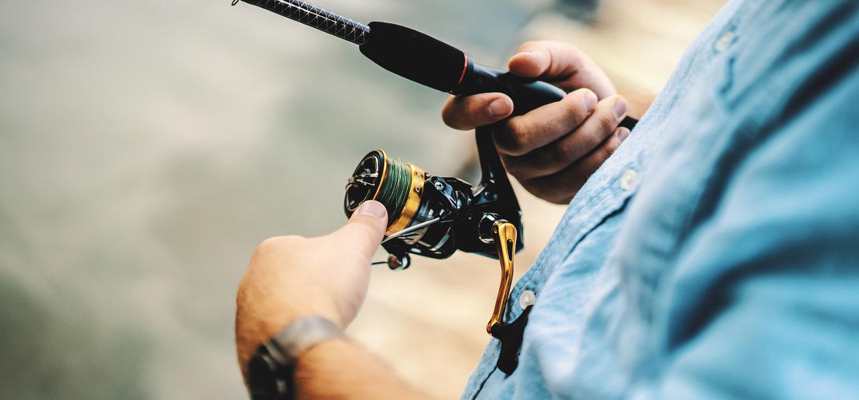 man reeling in fishing line