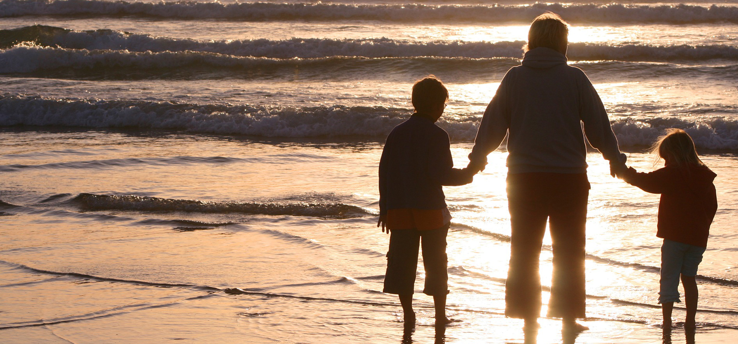 a parent holding their kids' hands at the beach during sunset