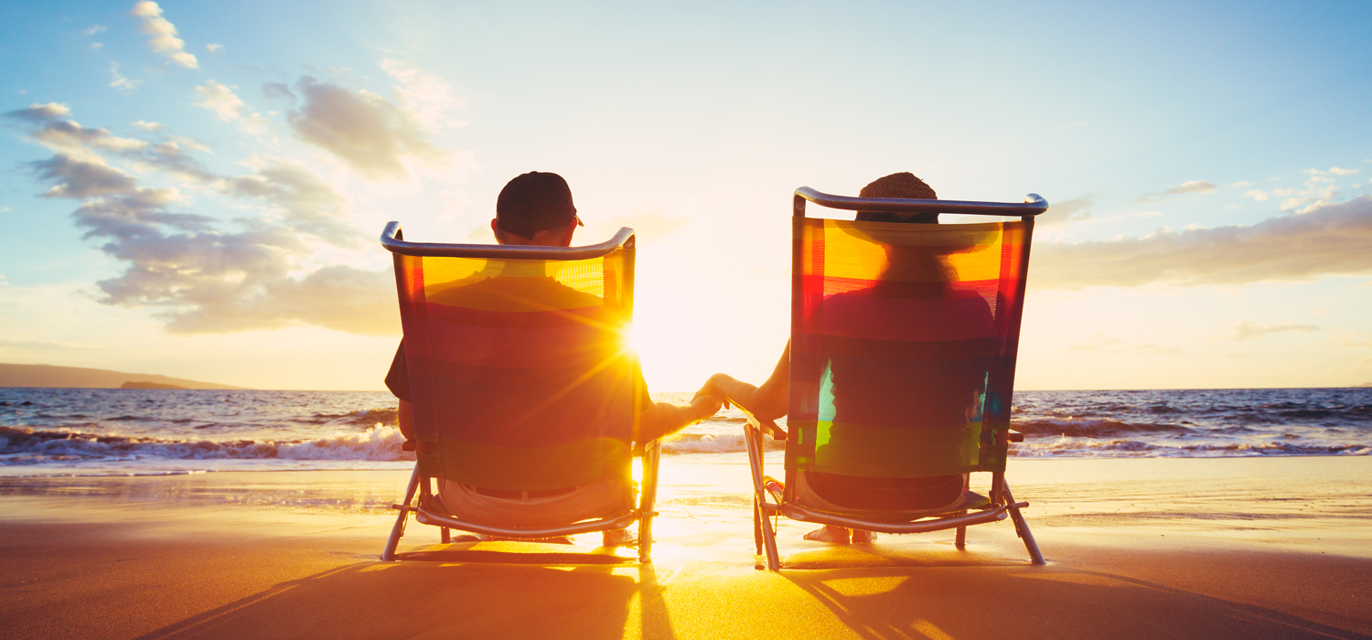 couple lounging on the beach at sunset