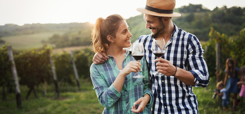 couple enjoying wine in a vineyard