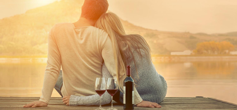 couple enjoys wine near the water on dock