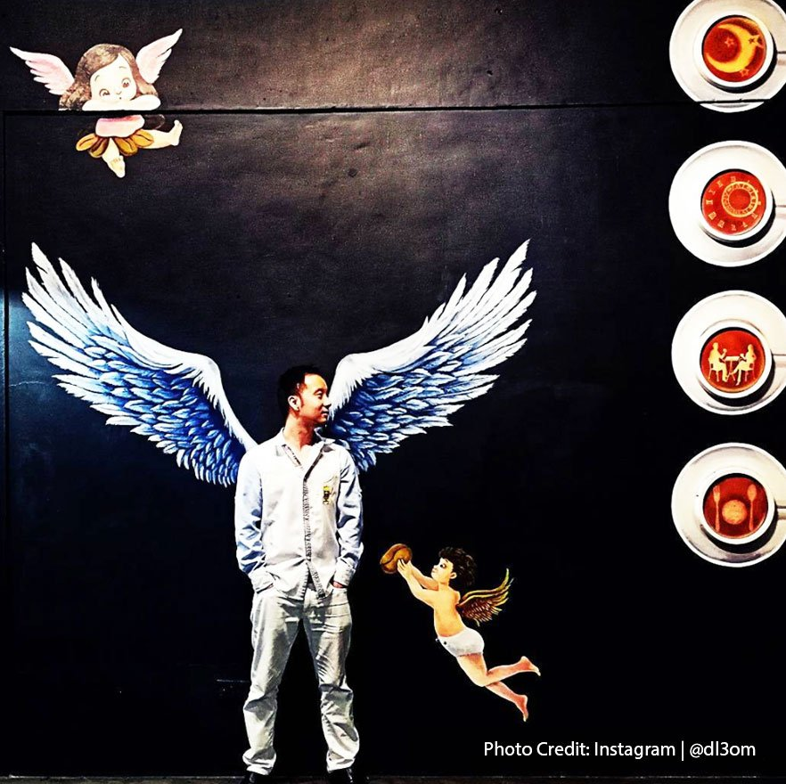 A man posing with mural paintings at Inns J Cafe, Port Dickson