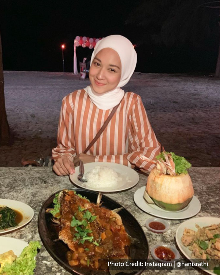 Woman posing in front of dishes at at Embok Village Steamboat and Seafood, Port Dickson