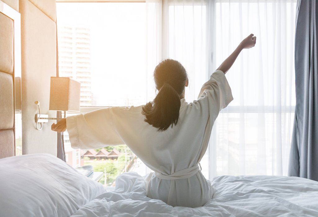 woman stretching in bed in the morning