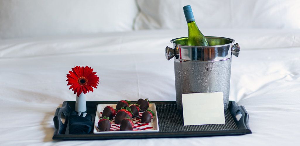strawberries and champagne on hotel room bed