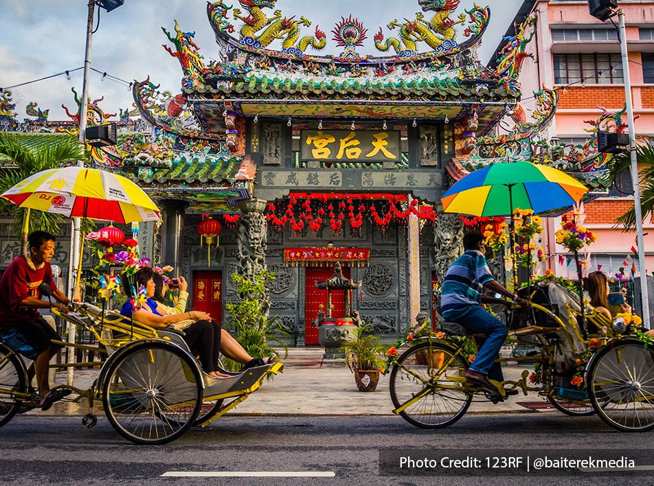 Front view of a Chinese temple in penang with local tricycles