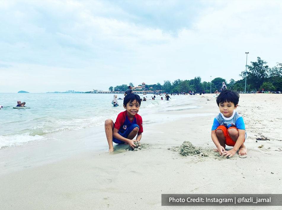 tourists having fun with their beach activities in Saujana Beach Port Dickson