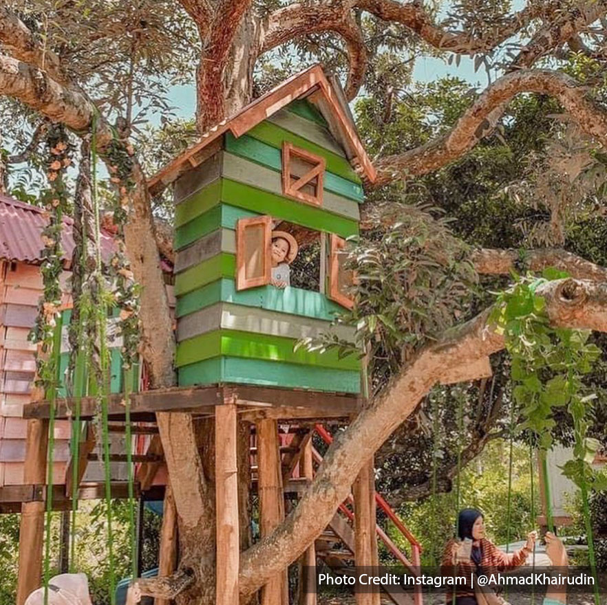Tourist in colourful farm treehouse
