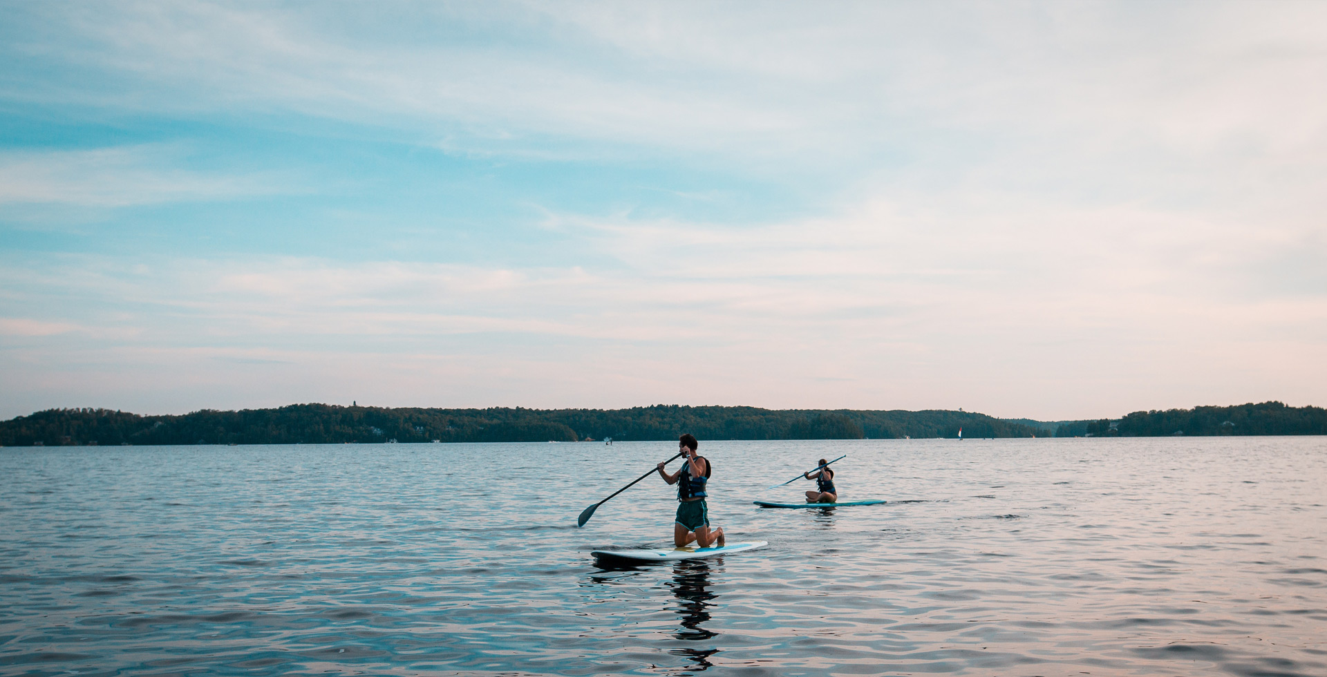 friends paddleboarding at dusk on a lake