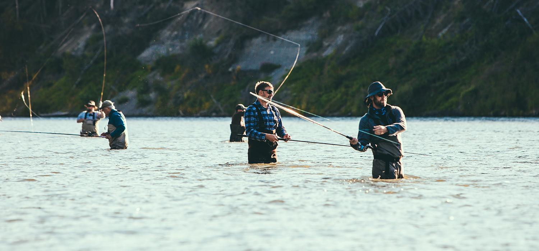 men fly fishing in a river