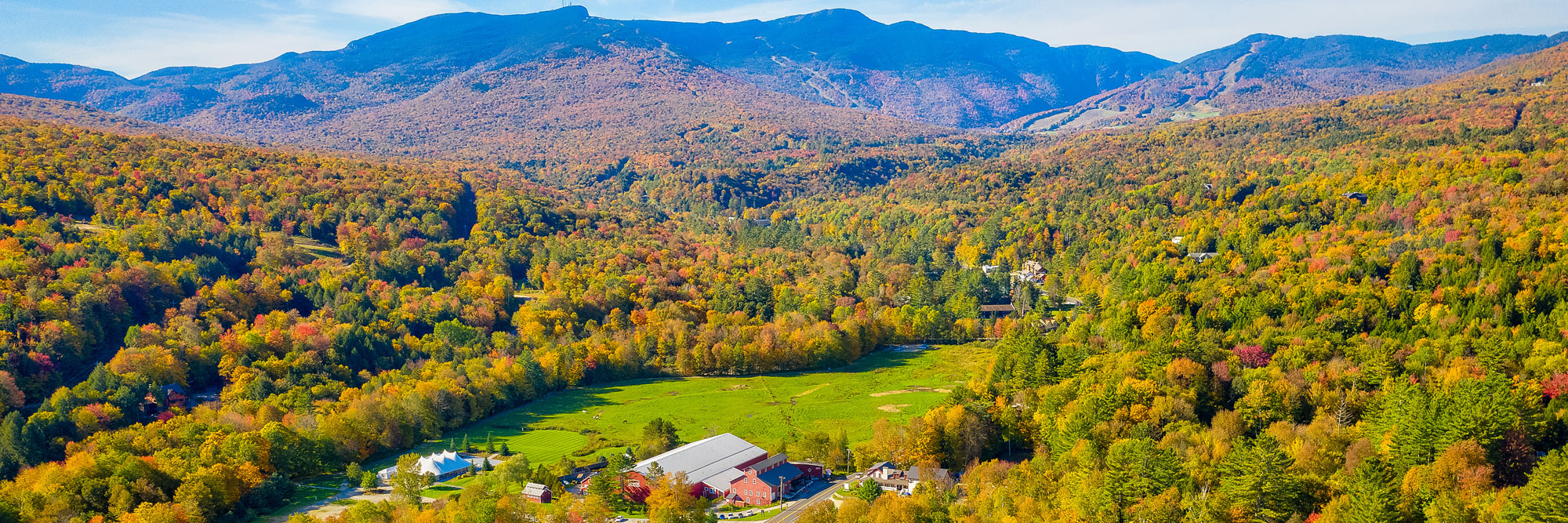 View of Mt. Mansfield and the Green Mountains covered in bright fall foliage.