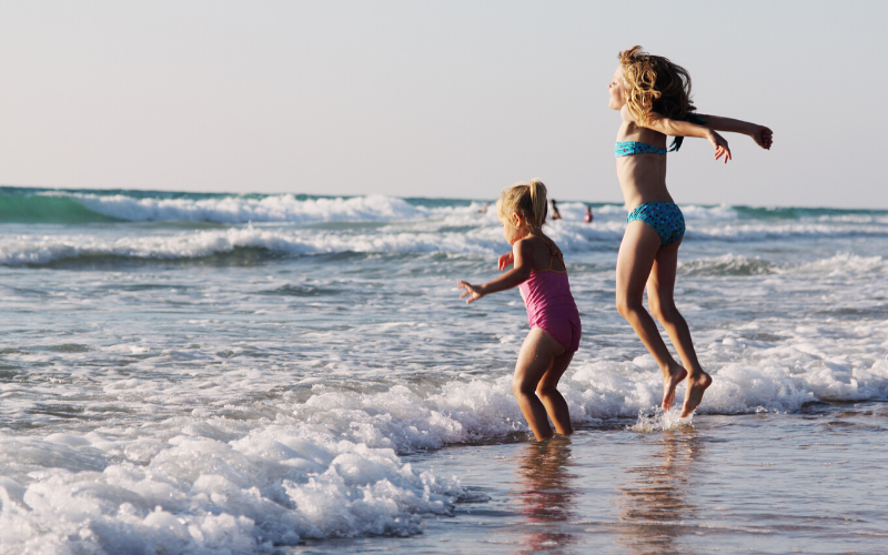 kids jumping waves on the beach