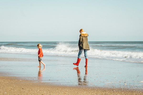 young family walking along beach Autumn