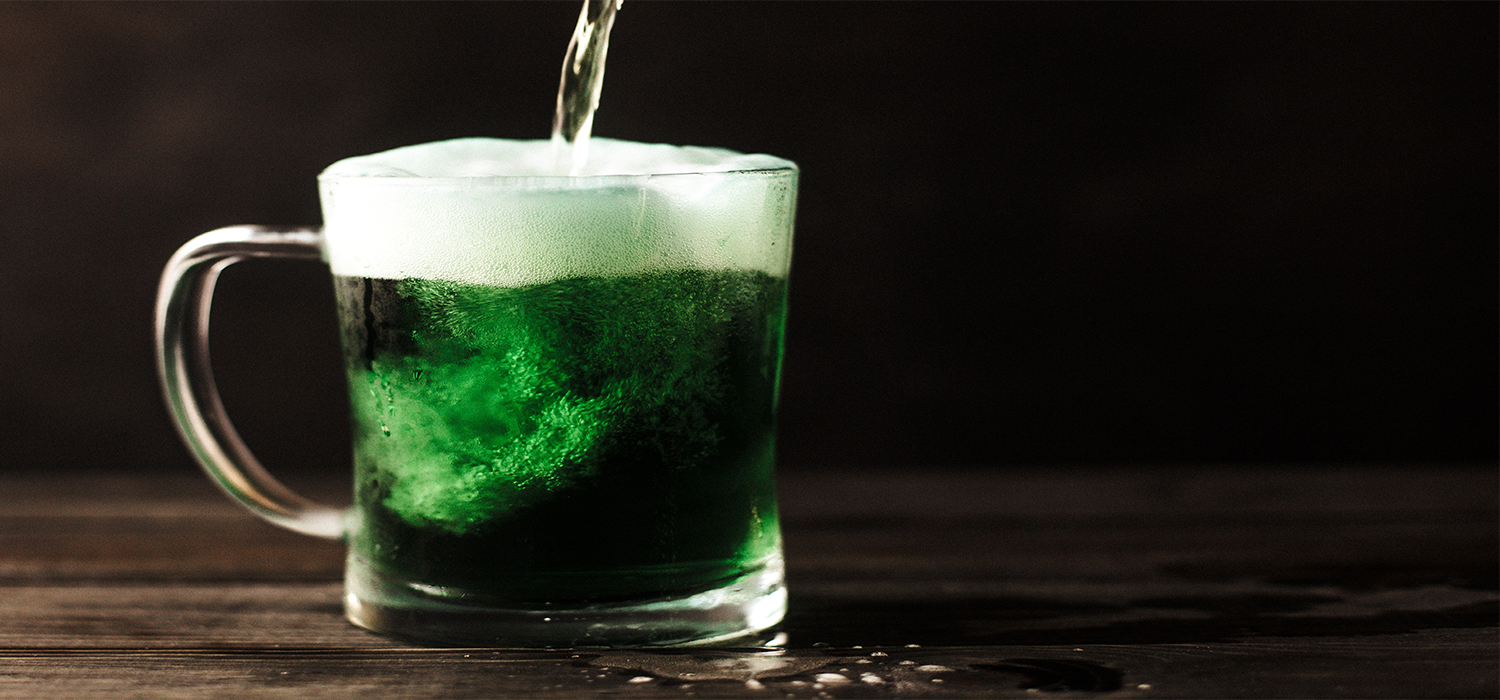 Green beer being poured on a wooden table in celebration of St. Patrick's Day.