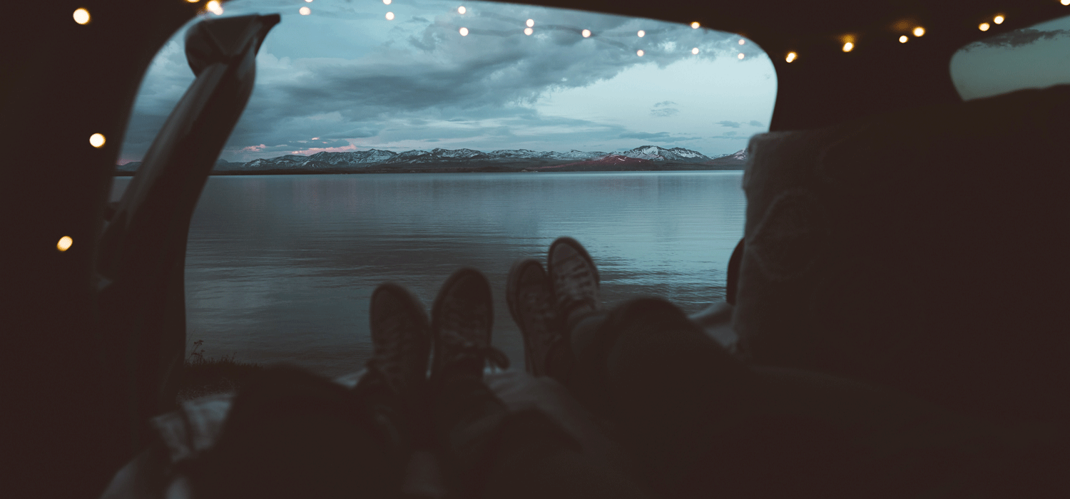 Camping in car by a lake with mountains