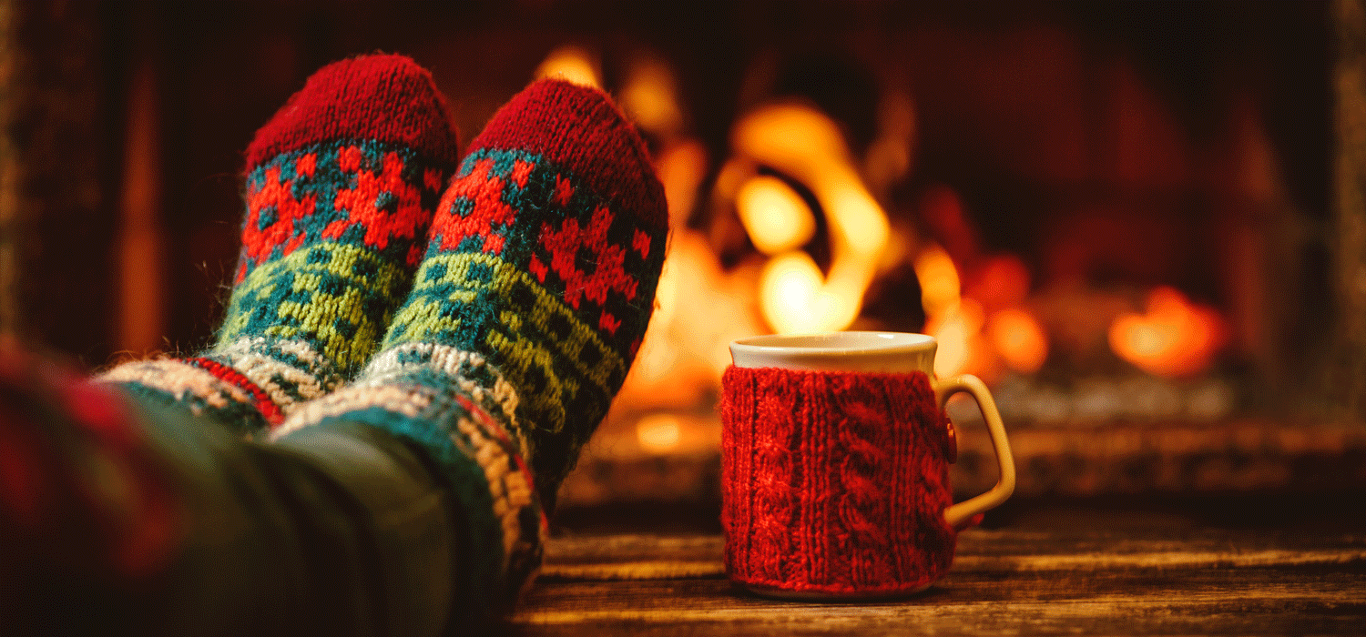 feet in cozy christmas socks in front of the fire