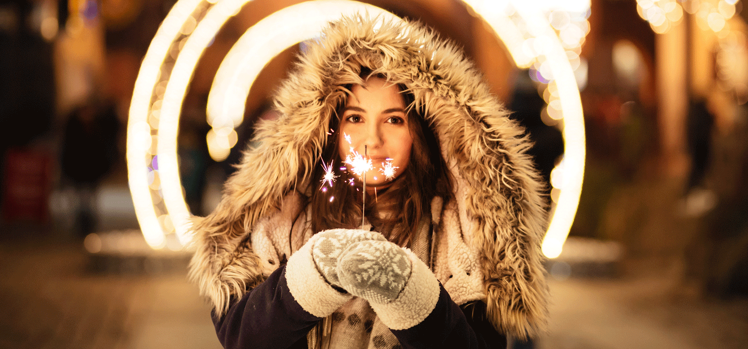woman holding sparklers in front of big lights
