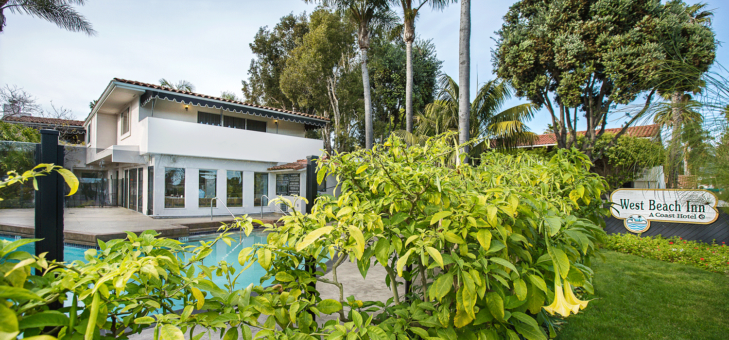 exterior view of lush West Beach Inn with pool view